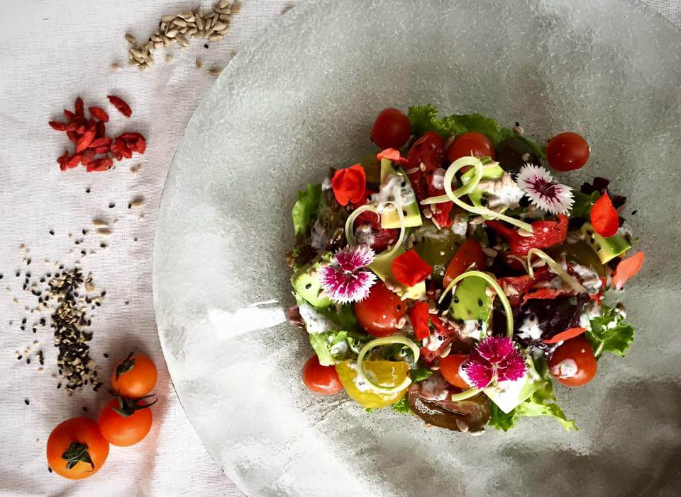 Fresca ensalada de tomates orgánicos en 4 formas- confitado, fresco, impregnado y asado con queso feta. Servida con palta, semillas y vinagreta ranch balanz