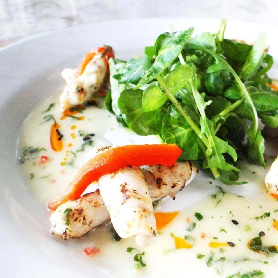 crujientes-calamares-a-la-parrilla-con-una-delicada-salsa-de-ajo-confitado-acompan%cc%83ado-de-frescas-hojas-de-arugula-bodega-d